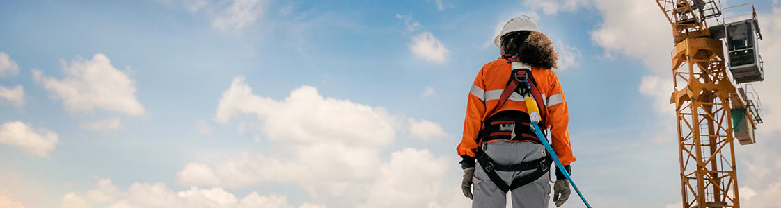 Contstruction woman wearing safety harness looking up at the sky